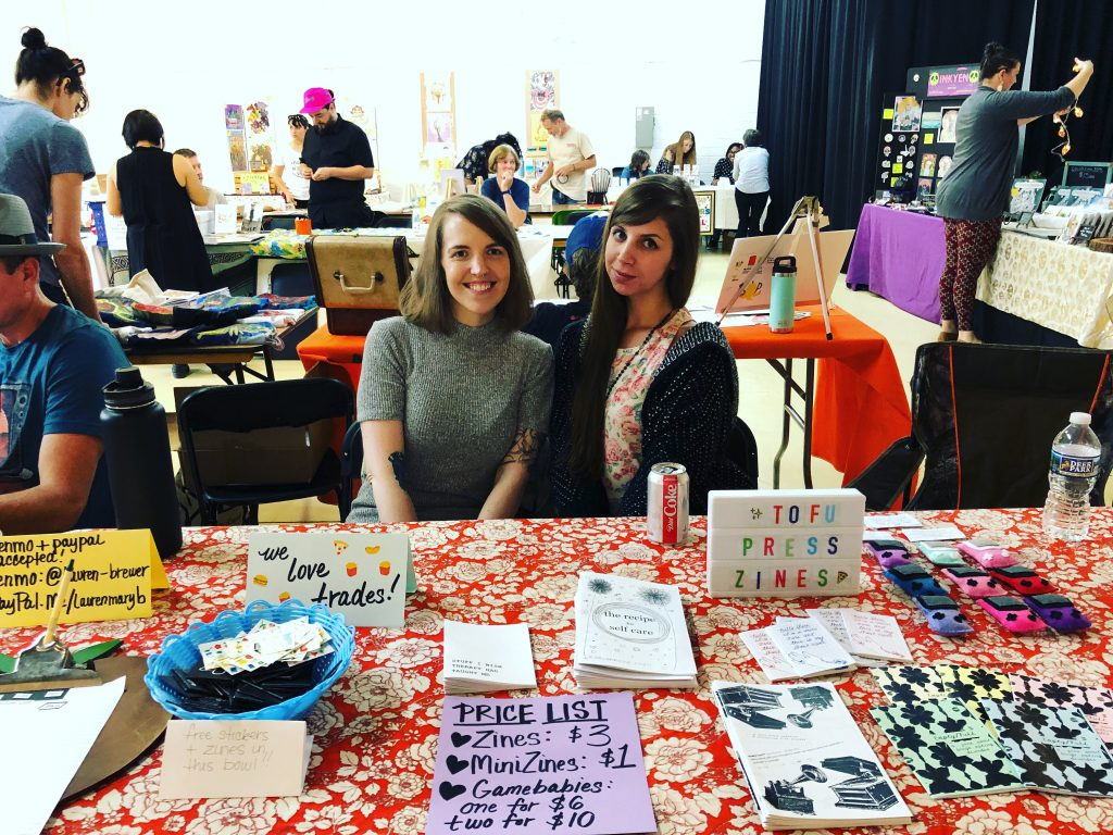 two white cis women sitting at a table, selling zines